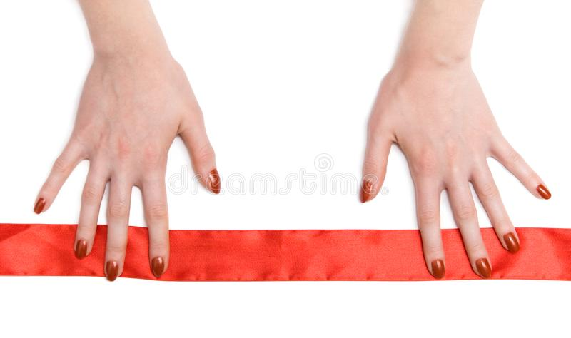 Woman hands with red ribbon. On white stock photography