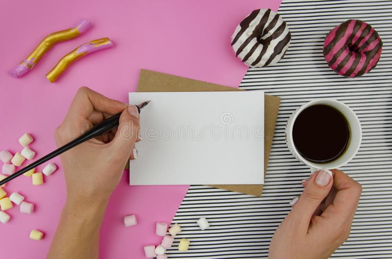 Woman hands with romantic letter.Top view, flatlay. Mockup template. Romantic morning motive, tea, rose and sweet donuts stock photo