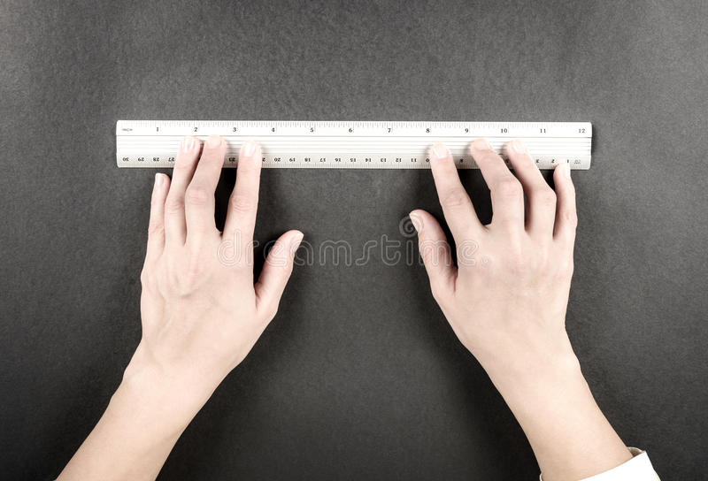 Woman hands with ruler. Two woman hands with silver ruler on black backround stock photo