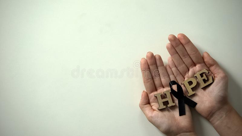 Woman hands showing black ribbon to camera, melanoma awareness, skin cancer royalty free stock photography