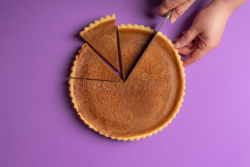 Woman hands slicing a pumpkin pie on a purple background. Minimalist culinary concept. Homemade sweet pie. Traditional holidays royalty free stock photography