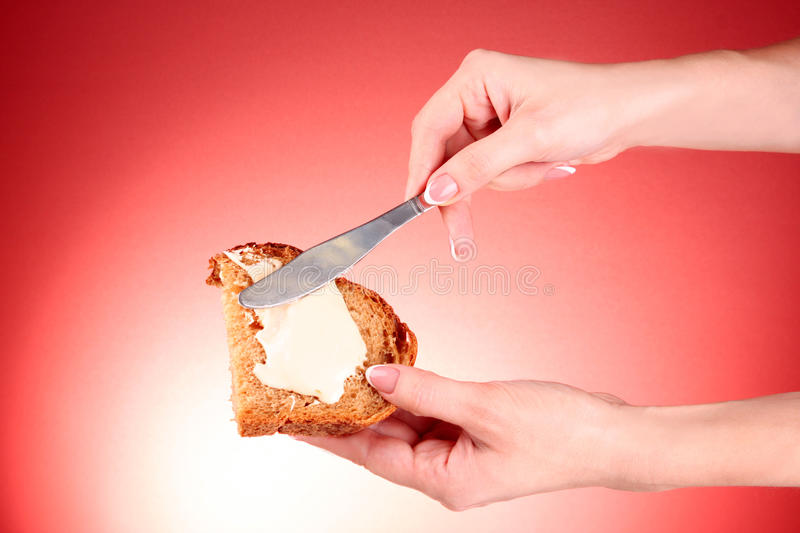 Woman hands spread bread with butter