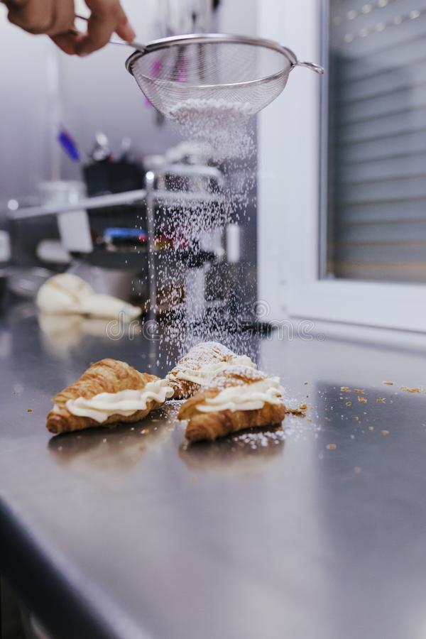 Woman hands sprinkling white flour over croissants on bakery royalty free stock image
