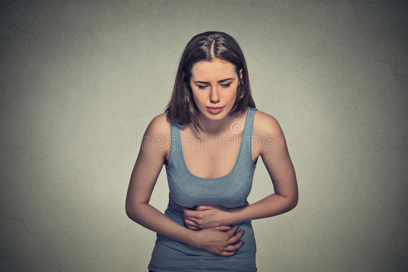 Woman hands on stomach having bad aches pain. Portrait young woman hands on stomach having bad aches pain isolated on gray wall background. Food poisoning stock image
