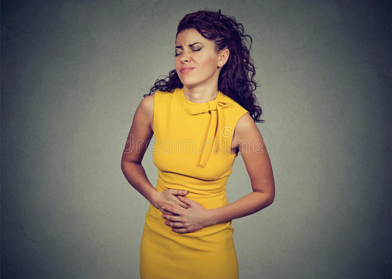 Woman with hands on stomach having bad aches pain. Young woman with hands on stomach having bad aches pain isolated on gray background. Food poisoning, influenza stock photos