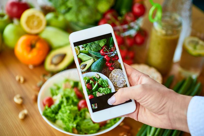 Woman hands take smartphone food photo of vegetables salad with tomatoes and fruits. Phone photography for social media or stock photo