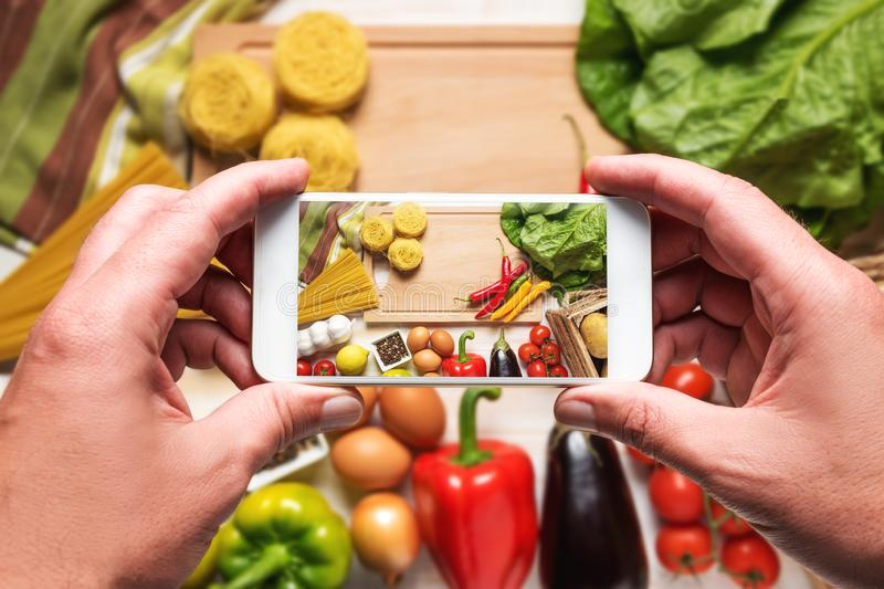Woman hands taking a photo of colorful vegetables and noodles on wooden background. stock photo