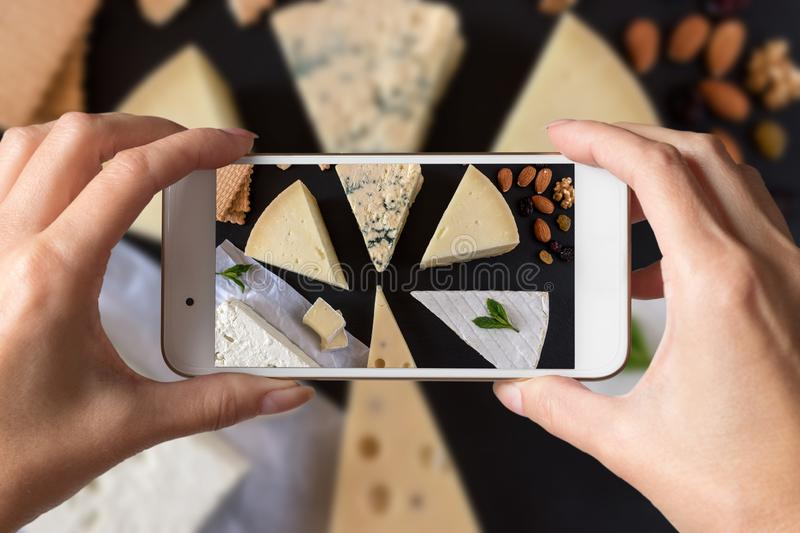 Woman hands taking a photo of different kinds of cheeses on black stone board with nuts and herbs stock photography