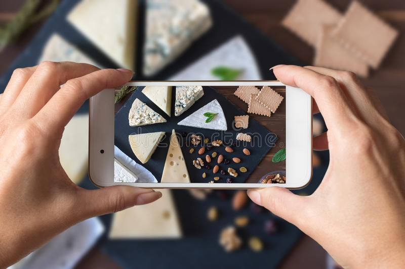 Woman hands taking a photo of different kinds of cheeses on black stone board stock photos