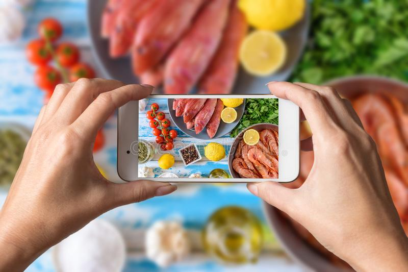 Woman hands taking a photo of fresh shrimps and red mullet fish royalty free stock images