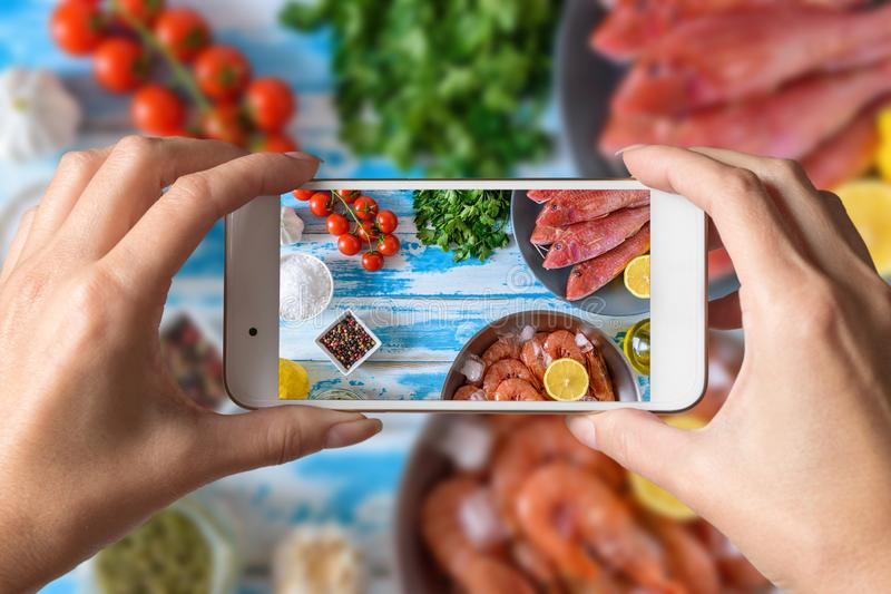 Woman hands taking a photo of fresh shrimps and red mullet fish on blue wooden background stock photography