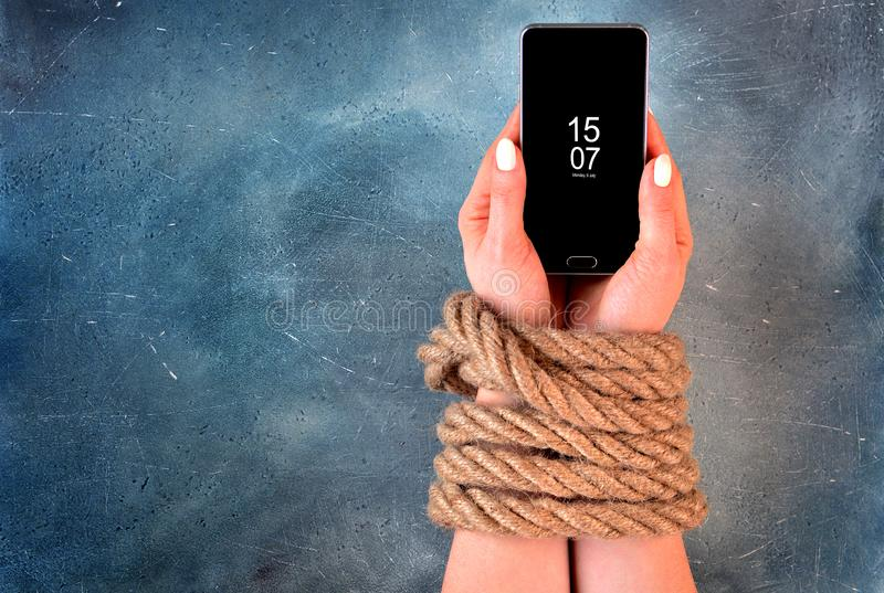 Woman hands tied with rope on a concrete background suggesting internet or social media addiction or captivity. Dependence on the smartphone idea royalty free stock images