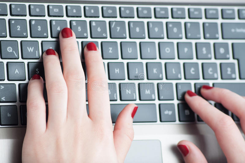Woman hands typing on laptop keyboard. Close up stock photography
