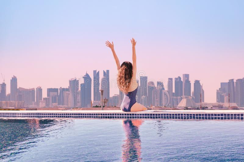 Woman with hands up enjoying morning view from roof top infinity pool at asia stock images