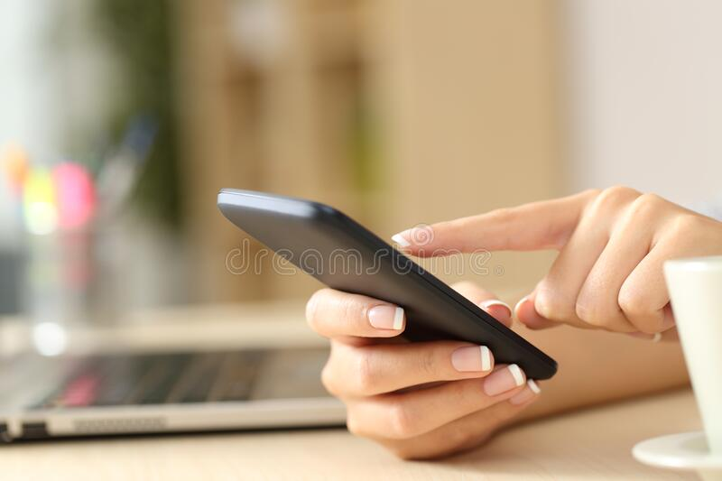 Woman hands using cell phone on a desk at home royalty free stock image