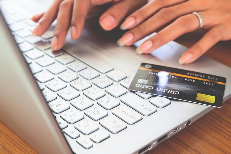 Woman hands using laptop computer with plastic credit card on keyboard. Selective focus . Online shopping, paying, buying. E-payment and technology concept stock photography
