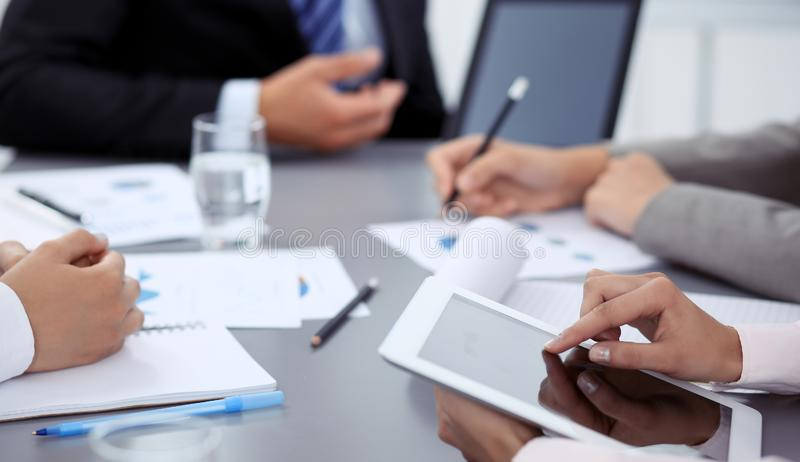 Woman hands using tablet at meeting. Business people group working together in office, close-up. Negotiation and. Communication concept stock photography
