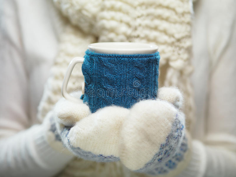 Woman hands in white and blue mittens holding a cozy knitted cup with hot cocoa, tea or coffee. Winter and Christmas time concept. Female hands holding knitted