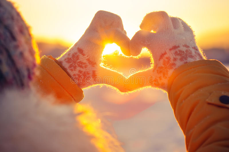 Woman hands in winter gloves Heart symbol shaped. Lifestyle and Feelings concept with sunset light nature on background