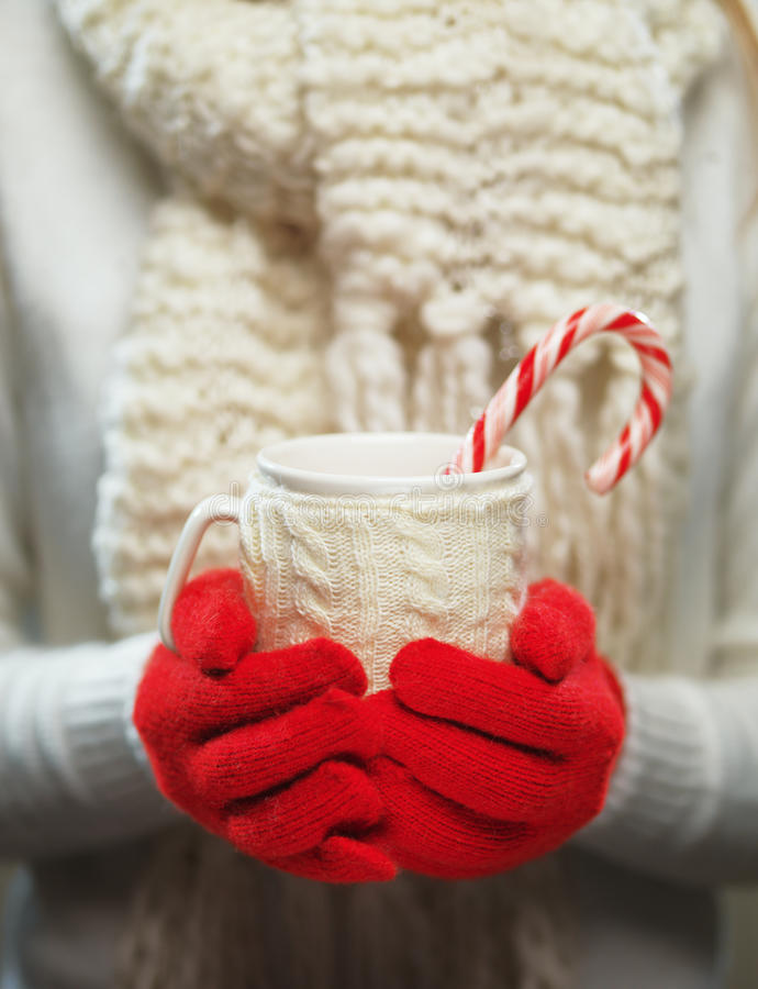 Woman hands in woolen red gloves holding cozy mug with hot cocoa, tea or coffee and candy cane. Winter and Christmas time concept. Woman holding winter cup stock photos