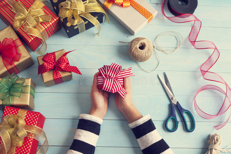 Woman hands wrap gift boxes stock photo