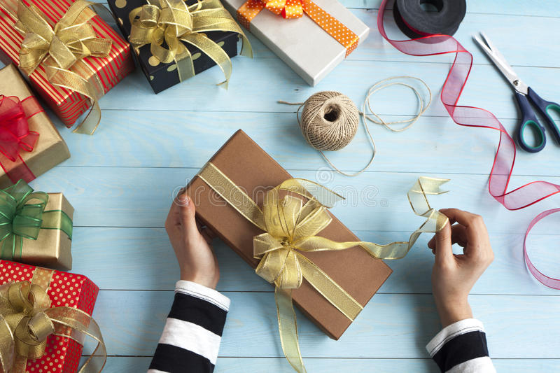 Woman hands wrap gift boxes stock images