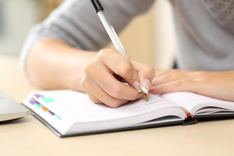 Woman hands writing notes on agenda on a desk stock images