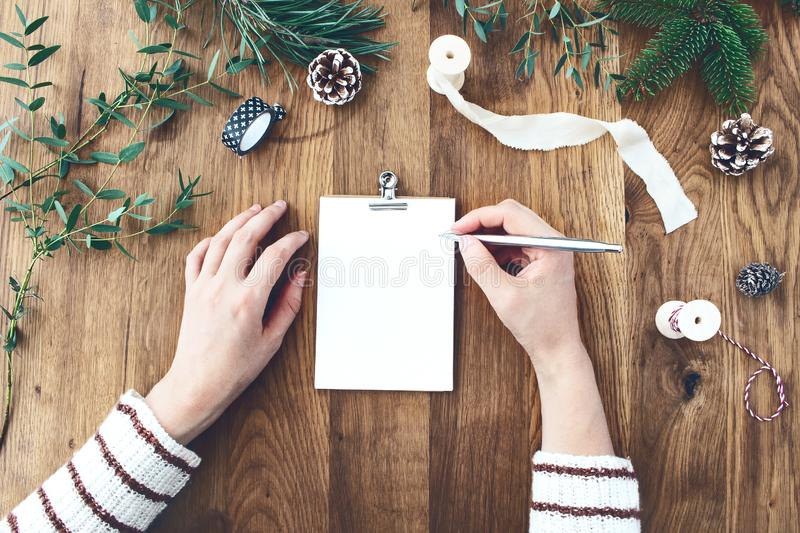 Woman hands writting Christmas wish list, goals, resolutions on empty letter card. Old oak wooden table with Christmas stock photo