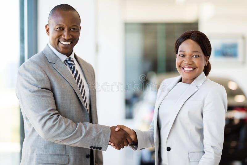 Woman handshaking car dealer. Beautiful african women handshaking with car dealer royalty free stock photos
