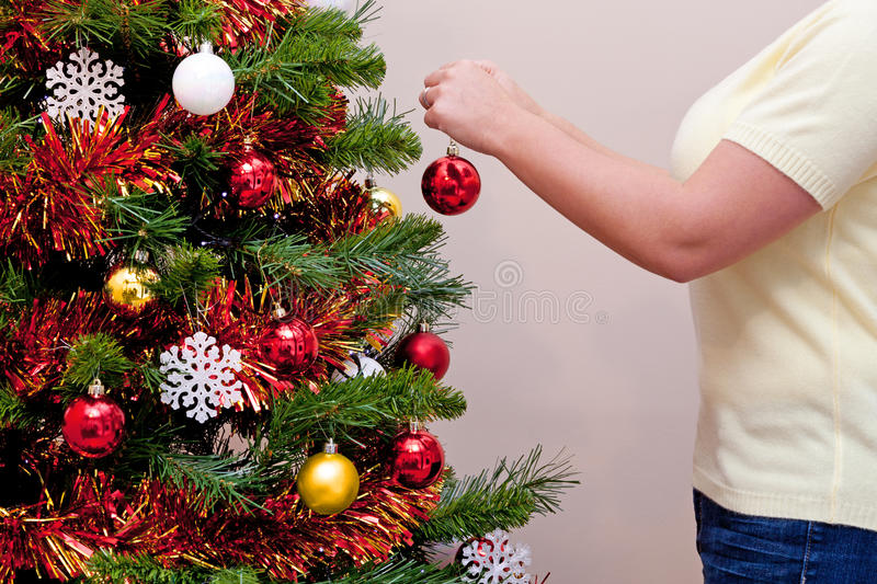 Download Woman Hanging A Baubel On A Christmas Tree Stock Image - Image: 27203613