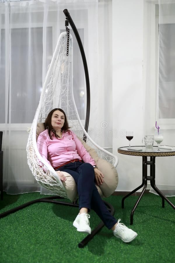 Woman in hanging chair stock photo