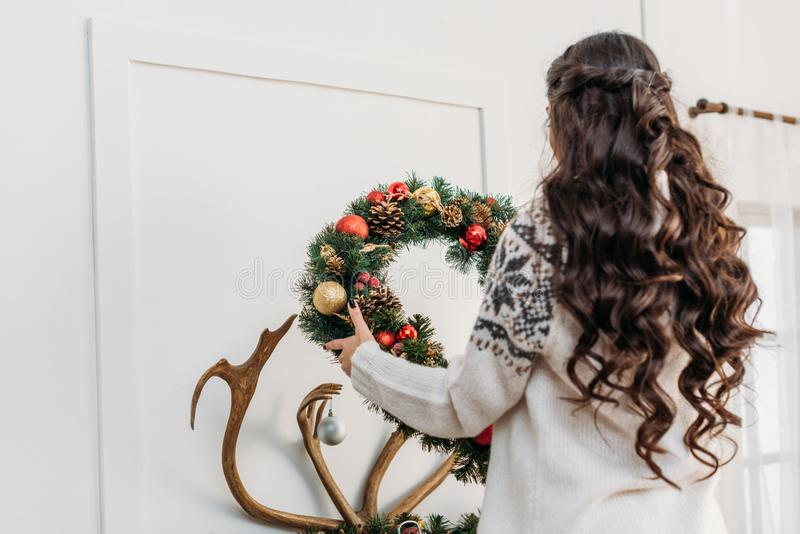 Woman hanging christmas wreath over fireplace. Woman in warm sweaters hanging christmas wreath over fireplace with antlers stock image