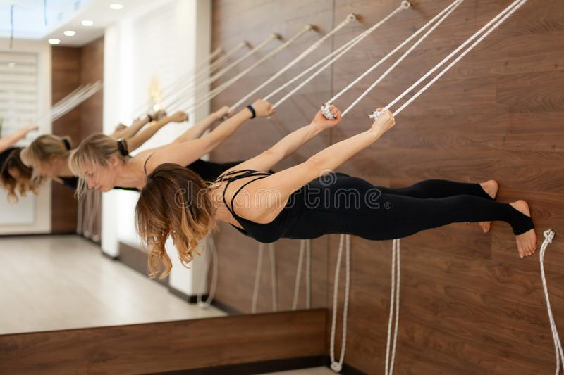 Woman hanging on clothesline parallel to the ground face down practicing yoga on stretch marks in the gym. Fit and wellness. Lifestyle stock image