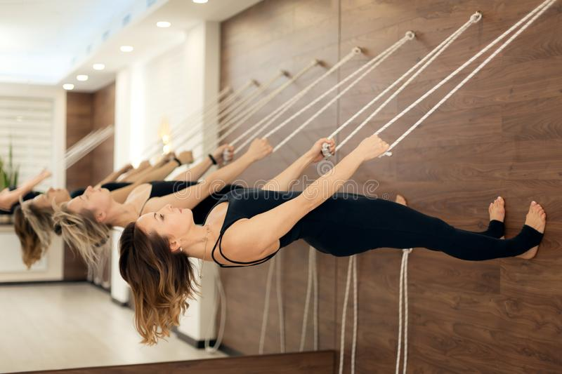 Woman hanging on clothesline parallel to the ground practicing yoga on stretch marks in the gym. Fit and wellness lifestyle.  stock photos