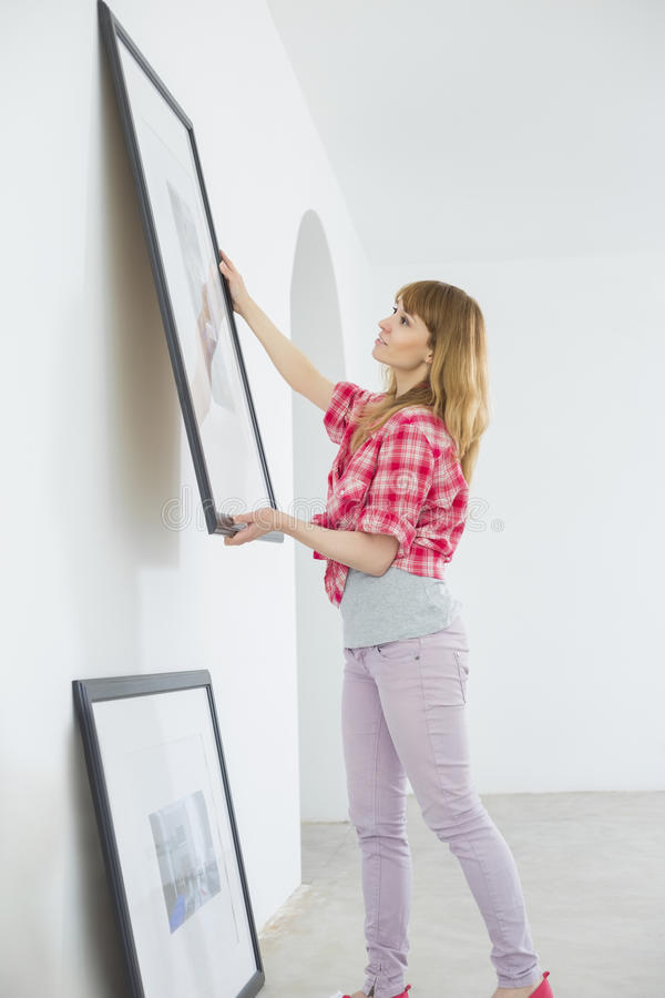 Free Woman Hanging Picture Frame On Wall In New House Royalty Free Stock Image - 45830066