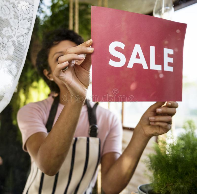 Woman hanging sale board on glass window royalty free stock images
