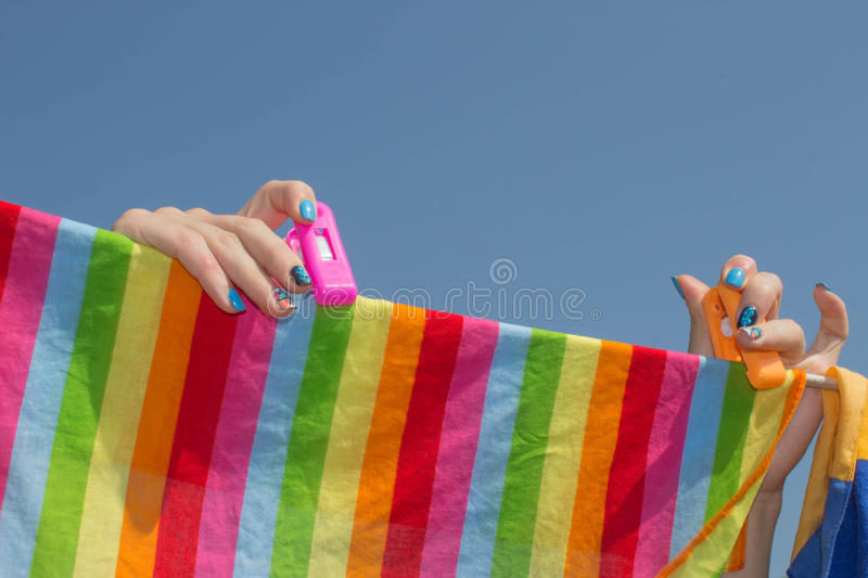 Woman hanging towel to dry on clothesline after laundry in the sun on blur nature background, good weather at summer or spring sea stock photo