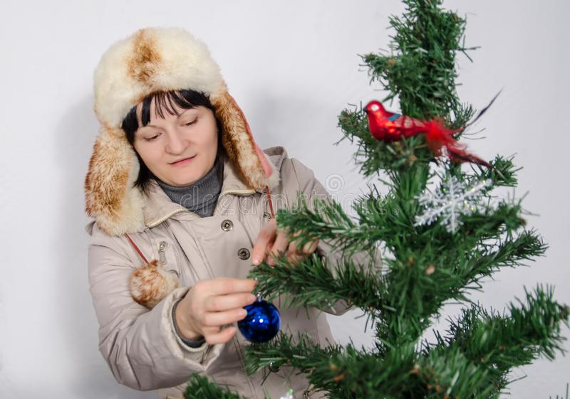 Woman hanging toys on a Christmas tree royalty free stock images