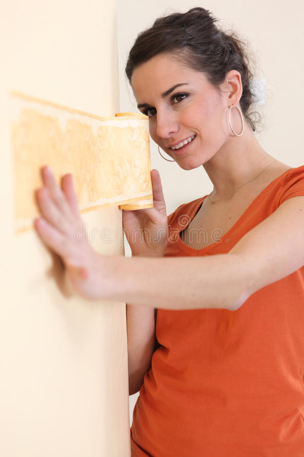 Woman hanging wallpaper. Woman putting wallpaper on a wall stock images