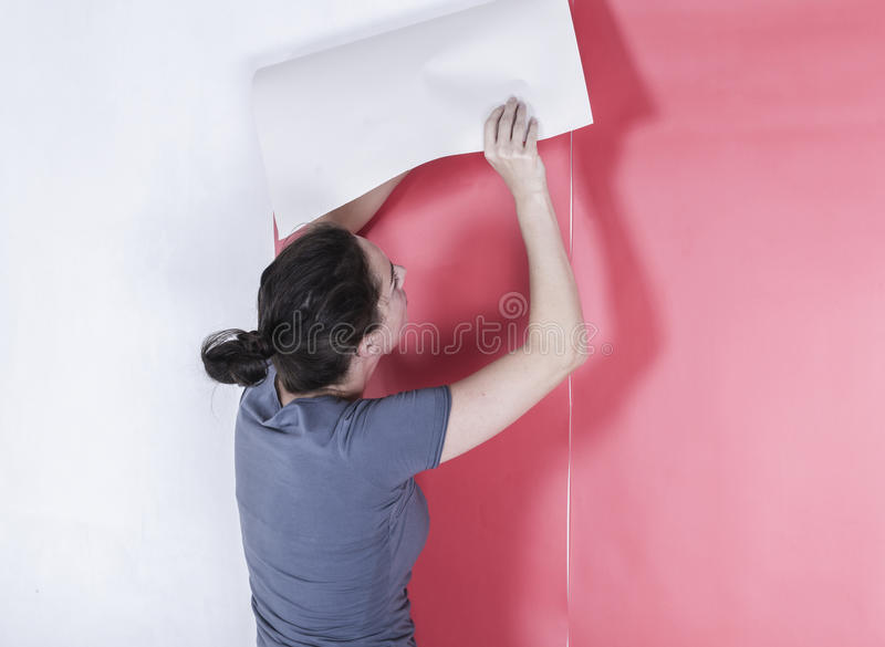 Woman hanging wallpaper. Decorating the wall doing home makeover stock image