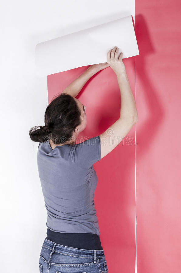 Woman hanging wallpaper. Decorating the wall doing home makeover stock photo