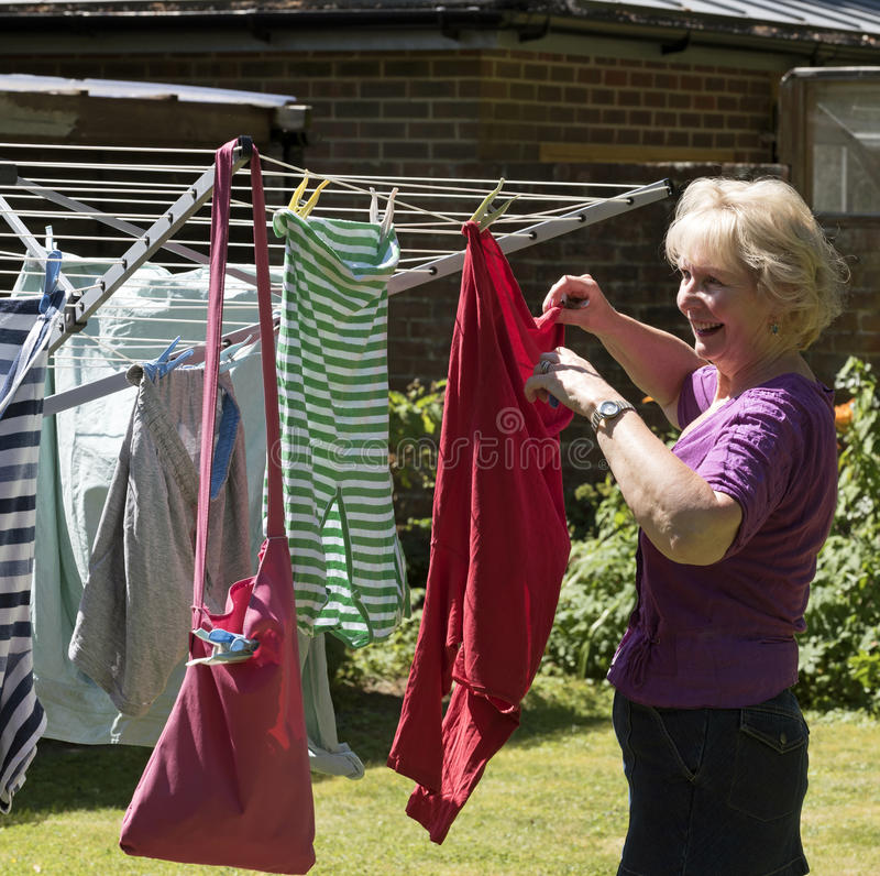 Woman hanging washing out to dry stock photo