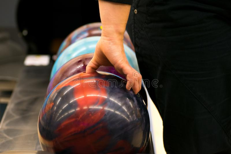 Woman harbors a bowling ball. Woman hangs a bowling ball to throw stock image