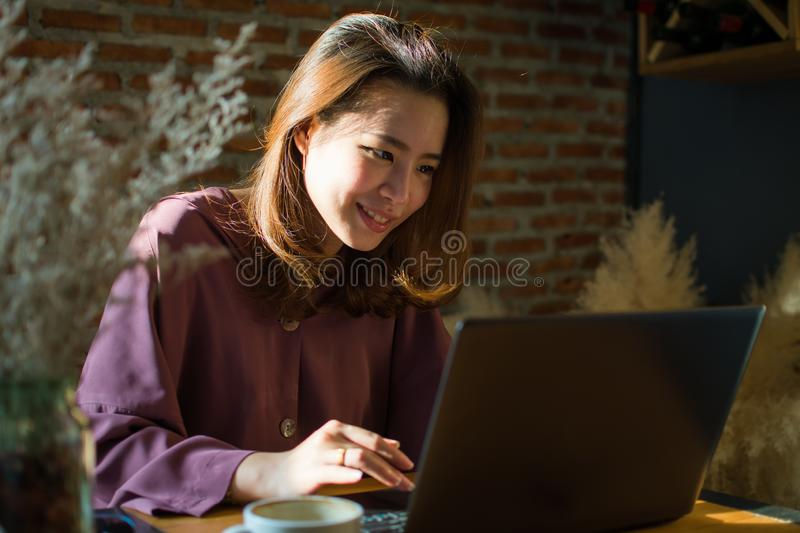 A woman is typing a message on her laptop. A woman is typing a message to someone by using her laptop, sitting in the coffee royalty free stock image