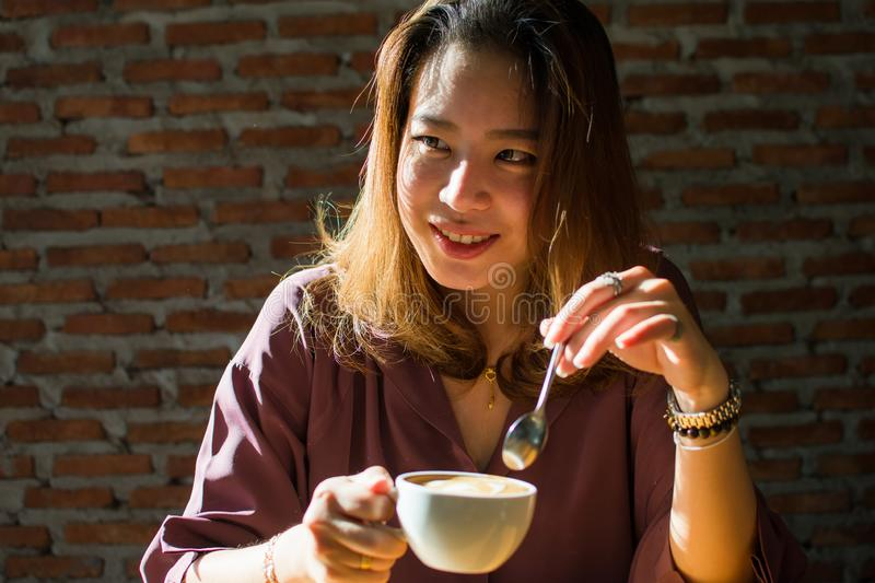 A pretty woman is looking at someone while drinking coffee royalty free stock photo