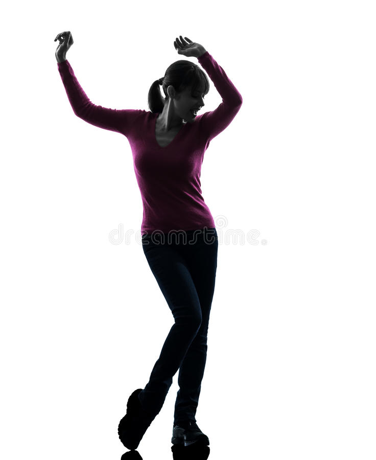 Woman happy dancing silhouette. One caucasian woman happy dancing in silhouette studio on white background stock photo