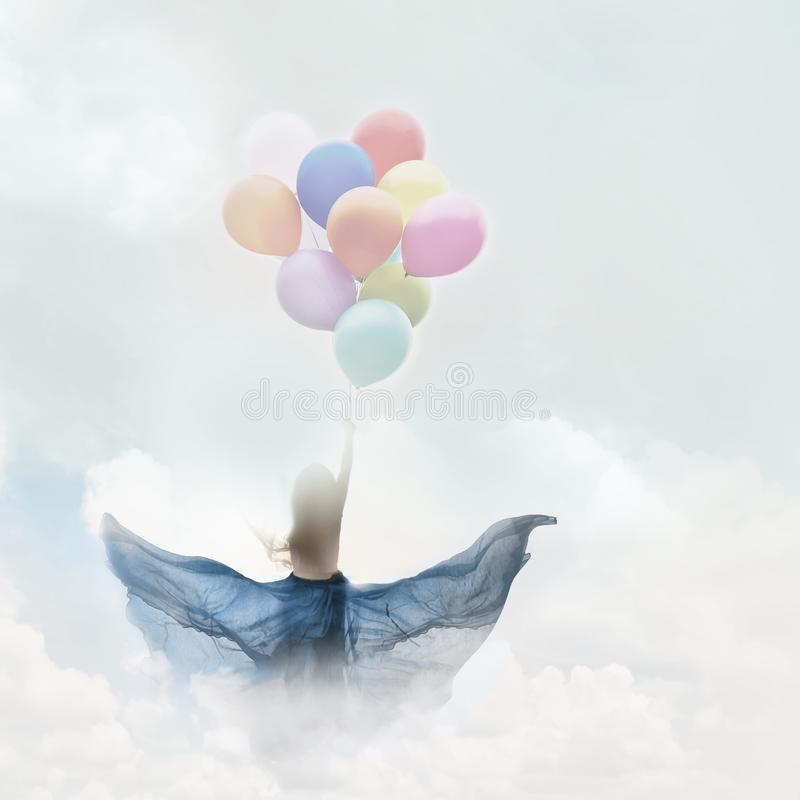 A woman in a happy dream. Flying in the sky lifted by colorful balloons stock photography