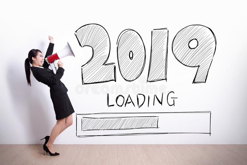 Woman happy with new year. Business woman talking in megaphone with 2019 new year on white wall background stock photo