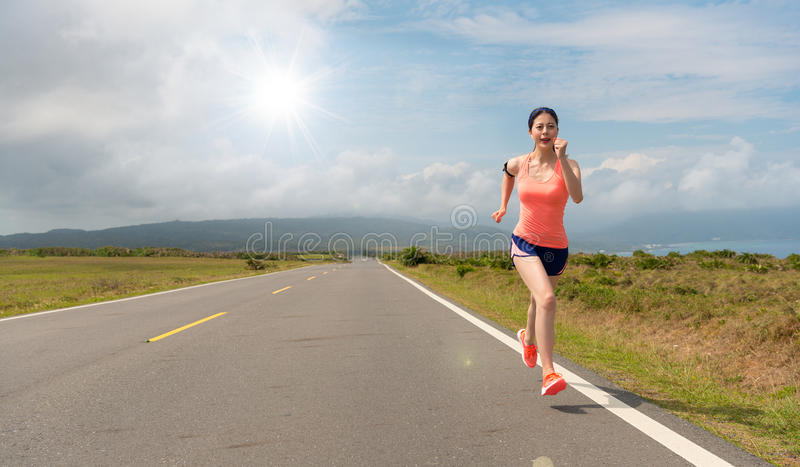 Woman happy running in the asphalt road movement. Young beautiful woman happy running in the asphalt road movement while the leisure time of the holiday with stock photography