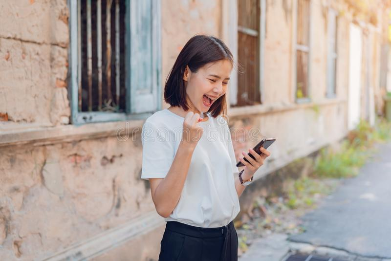 Woman of happy smiling and holding smart phone with amazed for success. royalty free stock photography